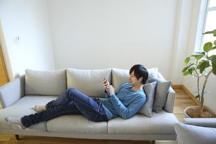 ソファで音楽を楽しむ若い男性の素材 [FYI00968651]