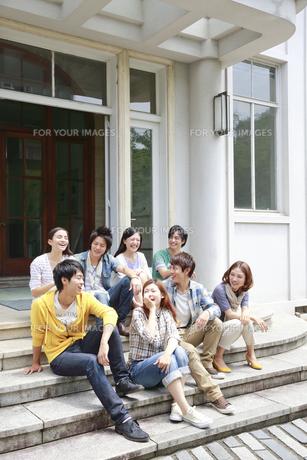 キャンパスに座って談笑する8人の男女大学生の素材 [FYI00968682]