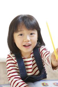 ペンを持つ笑顔の女の子の素材 [FYI00968745]