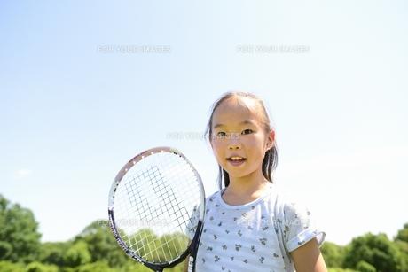 緑の草原とテニスラケットを持つ笑顔の女の子の素材 [FYI00969881]