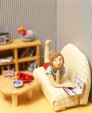 ソファに寝転び雑誌を見る女性のクラフトの素材 [FYI00986281]