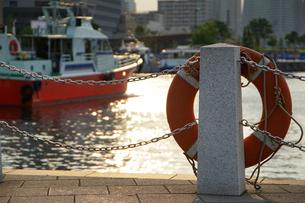 夕陽に照らされた横浜港の船と岸の浮き輪の写真素材 [FYI00986388]