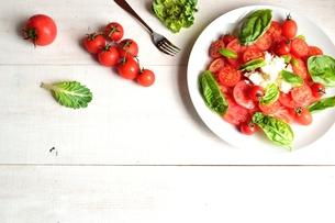 白皿に盛りつけたトマトとバジルのサラダ 白木材背景の写真素材 [FYI00986420]