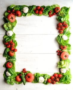 トマトとにんにくと葉野菜のフレーム 白木材背景の写真素材 [FYI00986454]
