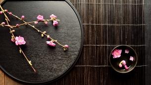 黒いおぼんの上の桃の花と小鉢の写真素材 [FYI00986500]
