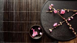 黒いおぼんの上の桃の花と小鉢の写真素材 [FYI00986501]