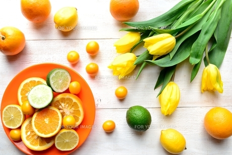 黄色いチューリップと柑橘系フルーツ 白木材背景の写真素材 [FYI00986837]