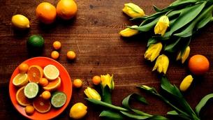 黄色いチューリップとお皿に盛り付けた柑橘系フルーツ 木材背景の写真素材 [FYI00986841]