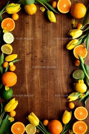 黄色いチューリップと柑橘系フルーツ フレーム 木材背景の写真素材 [FYI00986845]