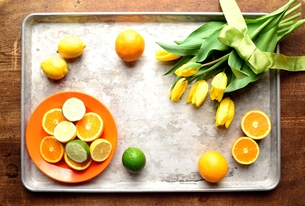 銀色のトレーにのせた黄色いチューリップと柑橘系フルーツの写真素材 [FYI00986854]