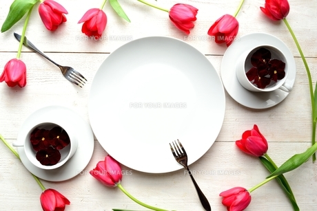 赤いチューリップとパンジーをアレンジした白食器 白木材背景の写真素材 [FYI00986905]