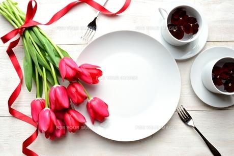 赤いチューリップの花束と二人分のペアの白い食器 白木材背景の写真素材 [FYI00986911]