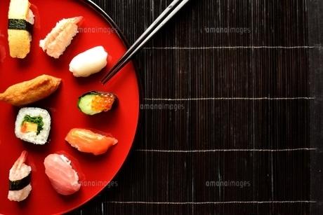 赤い漆塗りの皿に盛りつけたにぎり寿司と箸の写真素材 [FYI00987507]