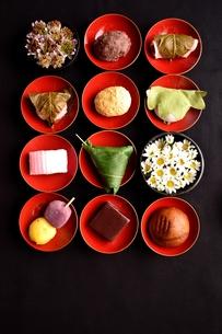 赤い杯に盛り付けた和菓子と小花の写真素材 [FYI00987520]
