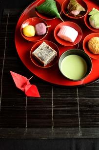 赤い杯に盛り付けた和菓子と折鶴と抹茶の写真素材 [FYI00987571]