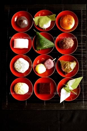 赤い杯に盛り付けた和菓子と折鶴の写真素材 [FYI00987579]