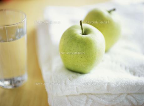 タオルにのった青りんごと水の入ったグラスの素材 [FYI00989317]