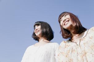 青空バックの二人の20代日本人女性の素材 [FYI00993991]