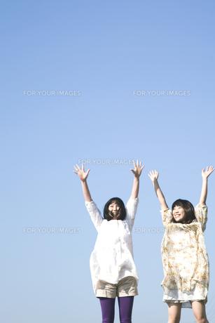 青空バックで万歳をする二人の20代日本人女性の素材 [FYI00993993]