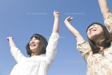 青空に向けて伸びをする二人の20代日本人女性の素材 [FYI00993997]