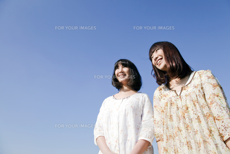 青空バックの二人の20代日本人女性の素材 [FYI00994036]