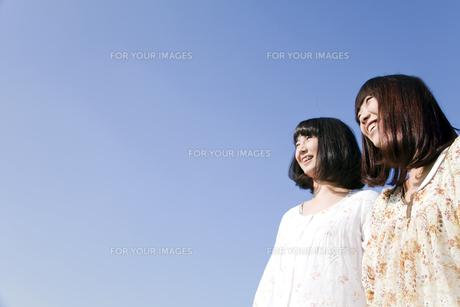 青空バックの二人の20代日本人女性の素材 [FYI00994080]