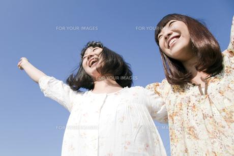 青空に向けて手を広げる二人の20代日本人女性の素材 [FYI00994154]