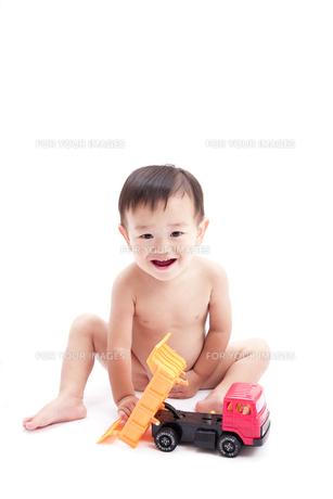 裸で座りトラックのおもちゃで遊ぶ赤ちゃんの素材 [FYI01016524]
