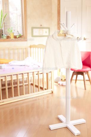 ベッドの前にあるハンガーにかけたベビー服の素材 [FYI01016672]
