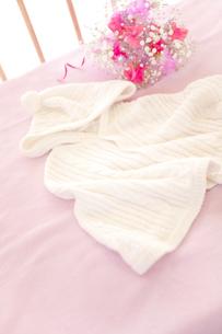 ベビーベッドの上のベビー服と花の素材 [FYI01016680]