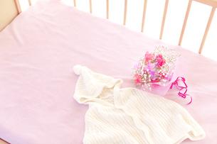 ベビーベッドの上のベビー服と花の素材 [FYI01016731]