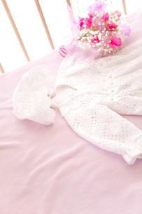 ベビーベッドの上のベビー服と花の素材 [FYI01016752]