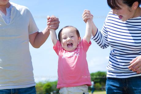 手を繋いで男の子を持ち上げる父と母の素材 [FYI01016828]