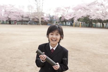 桜咲く校庭で卒業証書を持つ小学生の素材 [FYI01018436]