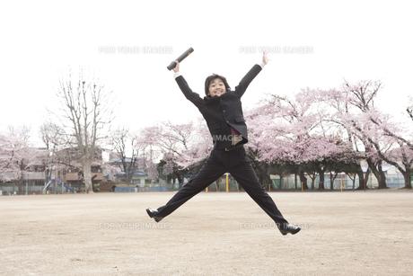 桜咲く校庭で卒業式にジャンプする小学生の素材 [FYI01018446]