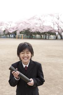 桜咲く校庭で卒業証書を持つ小学生の素材 [FYI01018476]