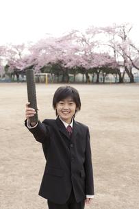 桜咲く校庭で卒業証書を持つ小学生の素材 [FYI01018484]