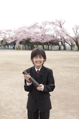 桜咲く校庭で卒業証書を持つ小学生の素材 [FYI01018510]