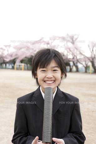桜咲く校庭で卒業証書を持つ小学生の素材 [FYI01018576]