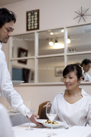 レストランで料理をサービスする人とテーブルの客の素材 [FYI01018683]