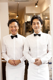レストランの入り口で客を笑顔で迎えるウエイターの素材 [FYI01018834]