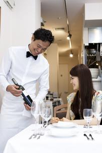 レストランでワインの説明をするウエイターと女性客の素材 [FYI01018905]