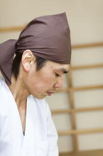 白い割烹着姿で仕事をする料理人の真剣な横顔の素材 [FYI01018932]