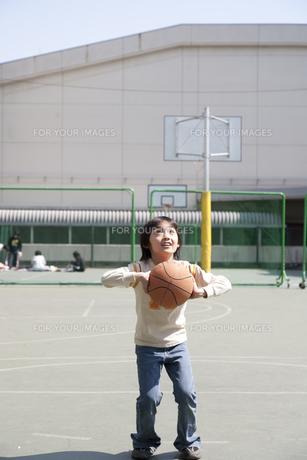 学校の校庭でバスケットボールをする男の子の素材 [FYI01018963]