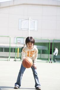 学校の校庭でバスケットボールをする男の子の素材 [FYI01019004]