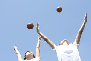 バスケットボールを空に投げる仲良し女子高生の素材 [FYI01019007]