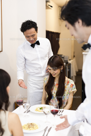 レストランで料理を出すウエイターのおもてなしと笑顔の女性客の素材 [FYI01019017]