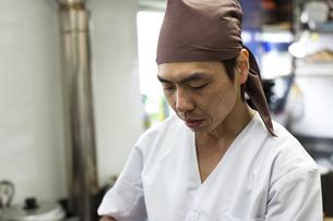 キッチンで白衣を着て作業をする料理人の素材 [FYI01019022]