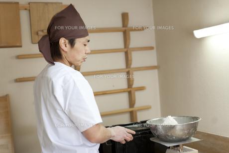 そば粉の量を測る料理人の横顔の素材 [FYI01019071]