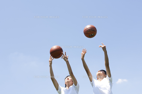 バスケットボールを空に投げる仲良し女子高生の素材 [FYI01019075]